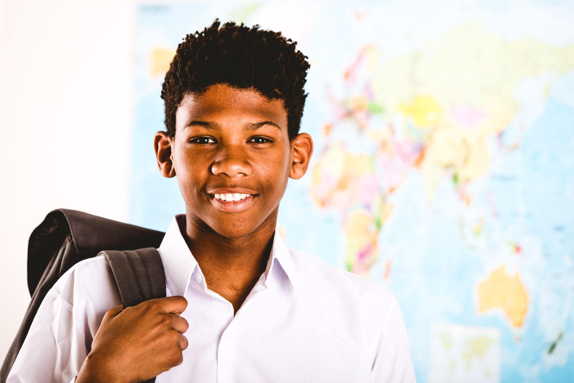 Young African boy in his school uniform and backpack standing in front of a world map grinning happi