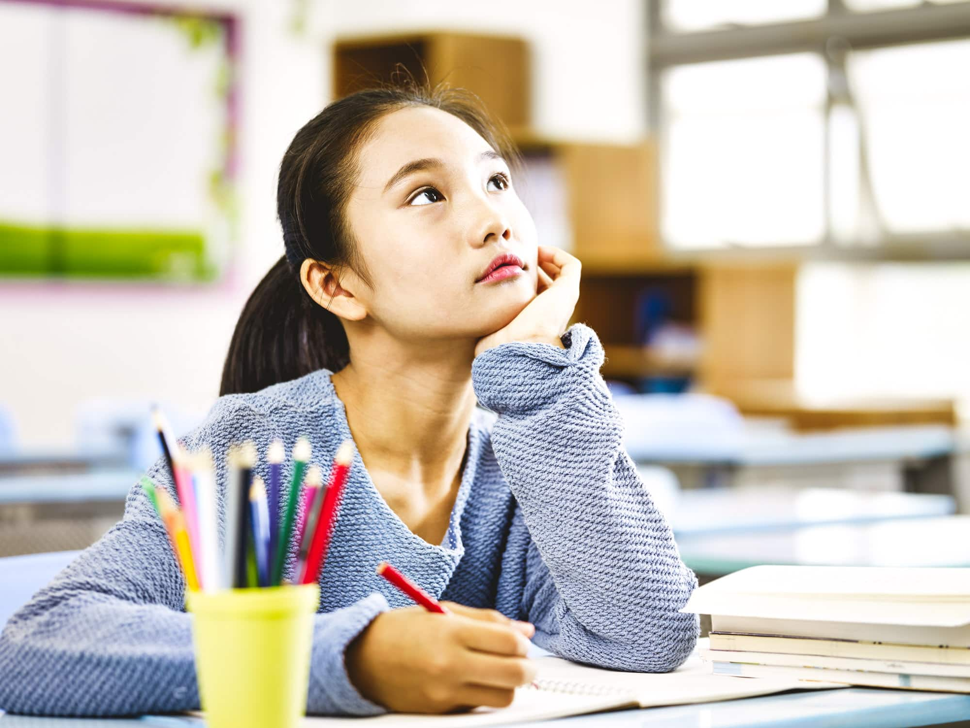 asian elementary schoolgirl looking up and thinking while studying in classroom_