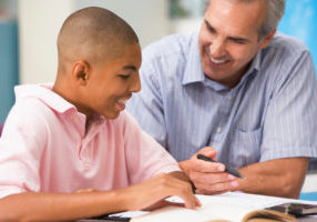 A teacher instructs a schoolboy in a high school class